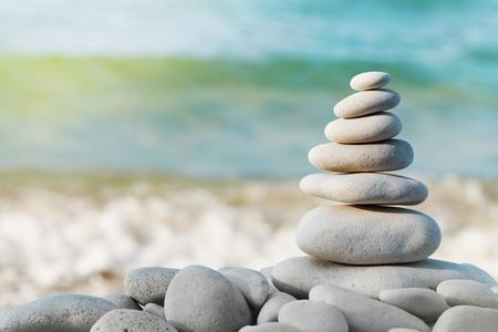 Foto de Stack of white pebbles stone against blue sea background for spa, balance, meditation and zen theme. - Imagen libre de derechos