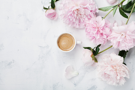 Photo pour Morning coffee and beautiful pink peony flowers on white stone table top view in flat lay style. Cozy breakfast on Mother or Woman day. - image libre de droit
