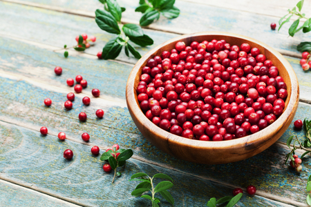 Photo for Ripe cowberry (lingonberry, partridgeberry, foxberry) in wooden bowl on rustic vintage background. - Royalty Free Image
