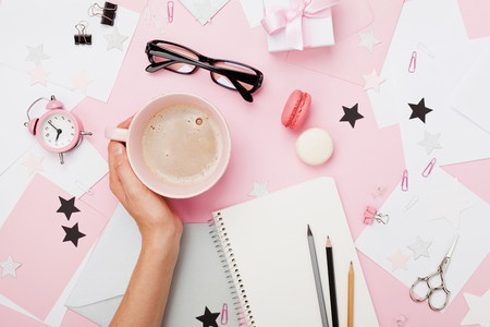Photo for female hand with coffee cup, macaron, office supply, gift and notebook on pastel desk top view. - Royalty Free Image