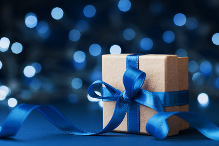 Photo pour Holiday gift box or present with bow ribbon against blue bokeh background. Magic christmas  greeting card. - image libre de droit