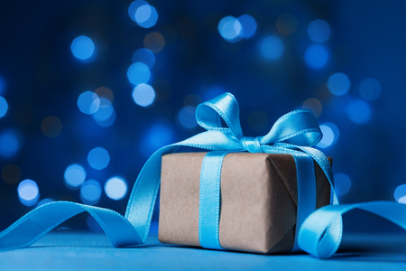 Photo pour Holiday greeting card. Christmas gift box or present with bow ribbon on magic turquoise bokeh background.  - image libre de droit