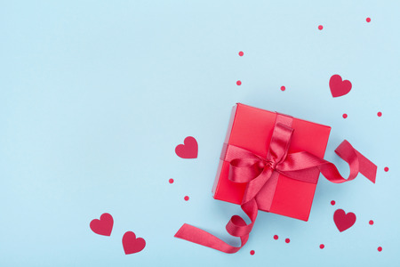 Foto de Present or gift box, paper heart and confetti on blue background top view. Valentines day greeting card. Flat lay style. - Imagen libre de derechos