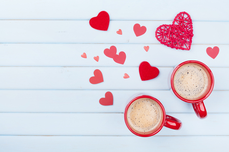 Foto de Two cup of coffee and mixed hearts on pastel blue table top view. Morning breakfast for Valentines day. Love concept. - Imagen libre de derechos