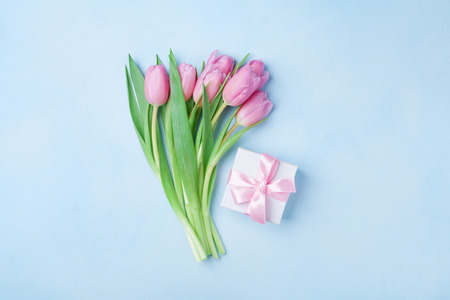 Photo for Spring tulip flowers and gift box on blue pastel table top view. Greeting card for Birthday, Womans or Mothers Day. Flat lay. - Royalty Free Image