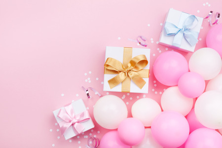 Photo for Birthday background with gift or present box, balloons and confetti on pink pastel table top view. Flat lay style. - Royalty Free Image