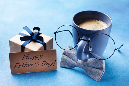 Photo pour Creative breakfast on Happy Fathers Day with gift box, funny face from cup of coffee, eyeglasses and bowtie. - image libre de droit