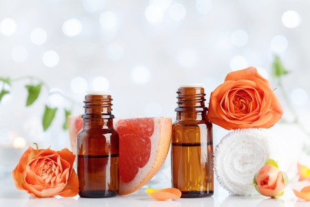 Photo for Essential oil bottles with towel, grapefruit and rose flowers on white table. Spa, aromatherapy, wellness, beauty background. Bokeh effect. - Royalty Free Image