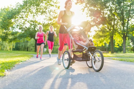 Photo pour Woman pushing her little girl in a toddler while running in nature with friends - image libre de droit