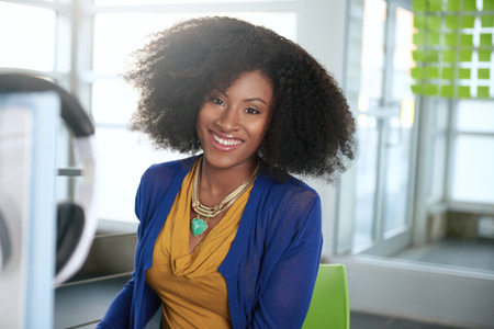 Photo for Friendly african american casual business woman working at a desktop computer in a modern withe office - Royalty Free Image