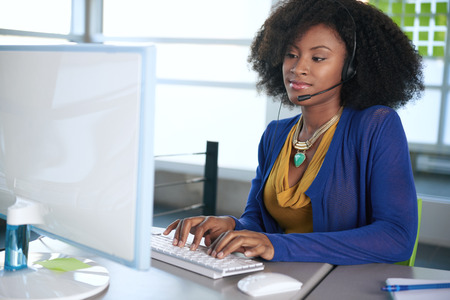 Photo pour Friendly african american casual call center emplyee working at a desktop computer in a modern withe office - image libre de droit