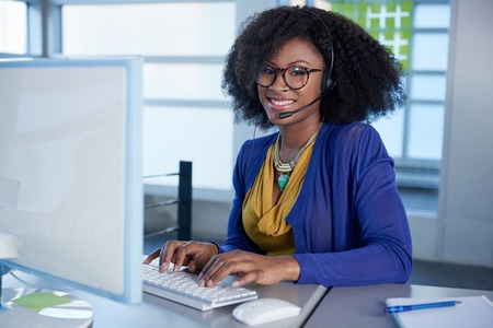 Photo for Friendly african american casual call center emplyee working at a desktop computer in a modern withe office - Royalty Free Image