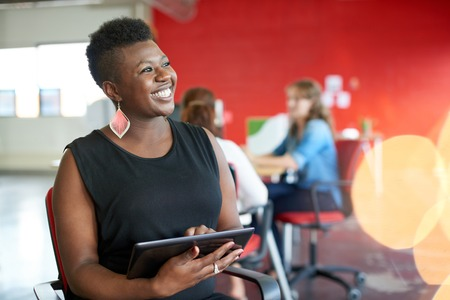 Photo pour Casual portrait of an african american business woman using technology in a bright and sunny startup with the team in the background - image libre de droit