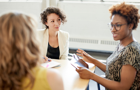 Photo for Candid picture of a female boss and business team collaborating. Filtered serie with light flares, bokeh, warm sunny tones. - Royalty Free Image