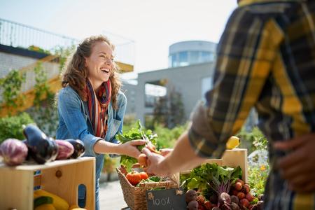 Foto de Friendly woman tending an organic vegetable stall at a farmers market and selling fresh vegetables from the rooftop garden - Imagen libre de derechos