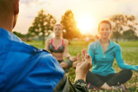 Photo pour Yoga class of diverse millennials on the grass at sunset in nature park - image libre de droit