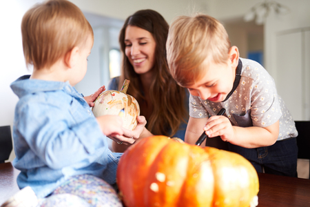 Foto de Family decorating pumpkins together for Halloween - Imagen libre de derechos
