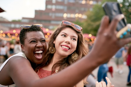 Photo for Diverse group of two girls taking selfies photos in the crowd of a summer music festival - Royalty Free Image