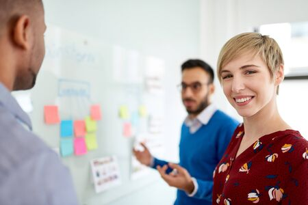 Photo pour Portrait of a smiling blonde short hair woman in a diverse team of creative millennial coworkers in a startup brainstorming strategies - image libre de droit