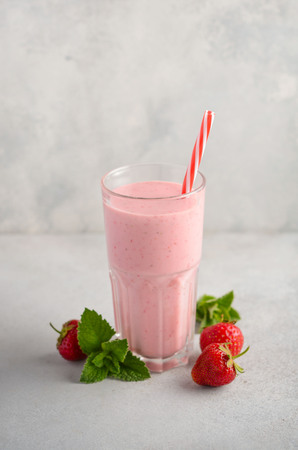 Foto de Strawberry milkshake on a gray concrete background, selective focus. - Imagen libre de derechos