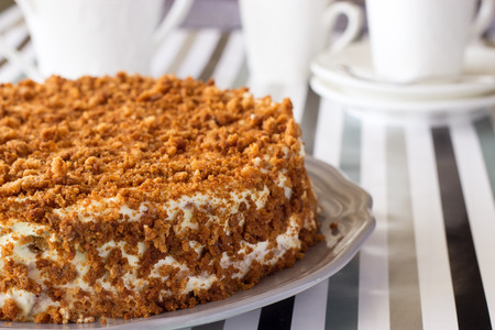 Photo for Homemade delicious honey cake with crumb. White tea set on background. Selective focus. - Royalty Free Image