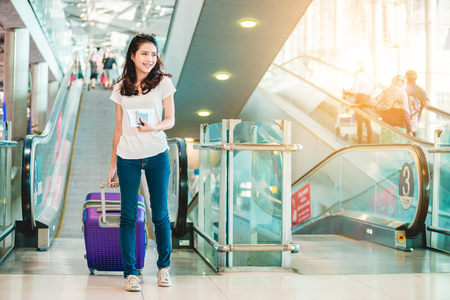 Photo pour Asian women were carrying luggage around the international airport. She was traveling abroad to travel on weekends. - image libre de droit