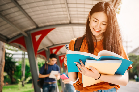 Photo for A young or teen asian girl student in university smiling and reading the book and look at the tablet or labtop computer in summer holiday. - Royalty Free Image