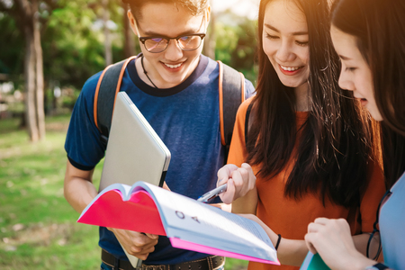 Photo for A group of young or teen Asian student in university smiling and reading the book and look at the tablet or laptop computer in summer holiday. - Royalty Free Image