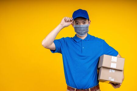 Foto de Young Asian handsome delivery man wearing mask holding boxs on left arm and touching his cap over yellow isolate background. Work from home and delivery concept. - Imagen libre de derechos