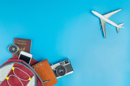 Foto de Backpacker travel accessories with plane fly pass on blue - Imagen libre de derechos