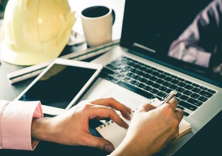 Foto de Engineer contractor working on laptop and notebook in office. - Imagen libre de derechos