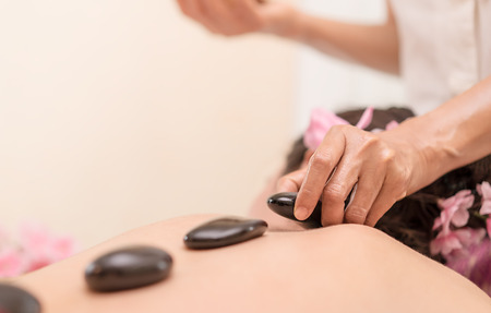Photo for Spa Therapist is placing hot stone on to women back - Royalty Free Image