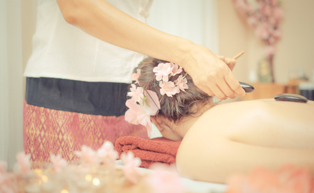 Photo for Spa Therapist is placing Hot stone on a Women back - Royalty Free Image