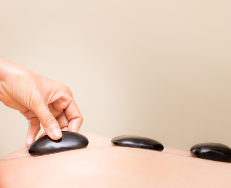 Photo for Hand is placing black hot stone on a women back - Royalty Free Image