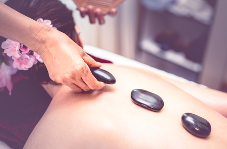 Photo for Spa Therapist is placing hot stone on to a women back - Royalty Free Image