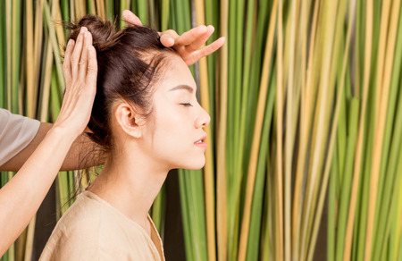 Photo for Women is having head massage relaxation on tree background - Royalty Free Image