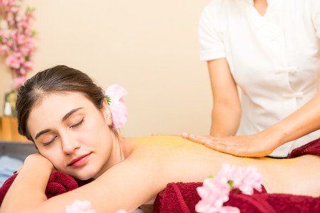 Photo pour Spa Therapist is rubbing Srub on to women back - image libre de droit