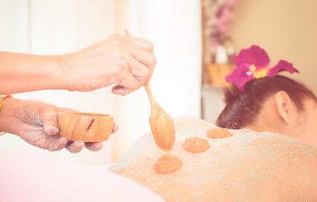 Photo pour Spa Therapist is putting Orange salt scrub on to a women back - image libre de droit