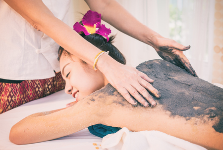 Photo pour Therapist is scrubbing Charcoal clay scrub cream on women back - image libre de droit