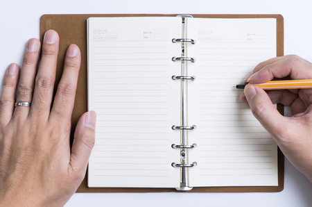 Photo pour Hand writing meeting and schedule on to an organizer notebook - image libre de droit