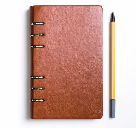 Photo pour Leather cover notebook with a yellow pen on white background - image libre de droit