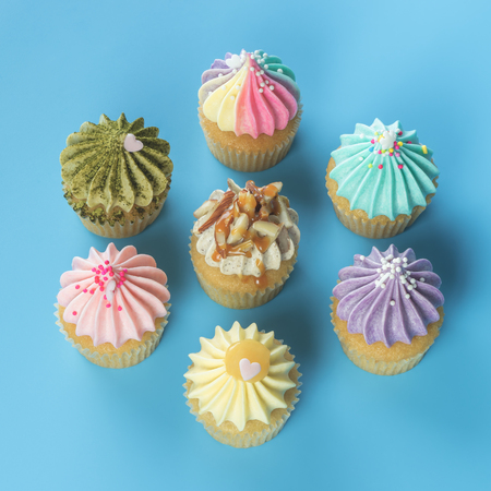 Photo for Fancy mini cupcakes top view on blue background - Royalty Free Image