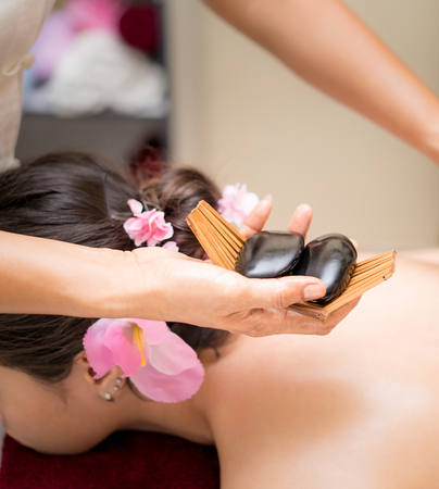 Photo for Spa therapist is putting Blank hot spa stone on to a woman back - Royalty Free Image
