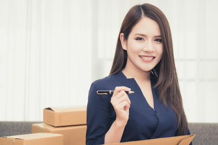 Photo for Pretty office business woman is preparing order packaging for customer - Royalty Free Image