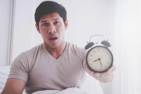 Photo pour Man just got up and shocked with late alarm clock - image libre de droit