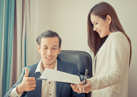 Photo for Business boss is giving complement to secretary business report - Royalty Free Image