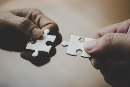Photo for Two hands joining together two jigsaw puzzles - Royalty Free Image