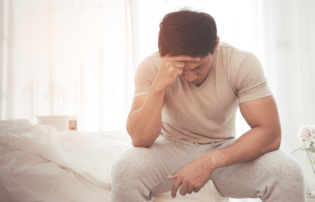 Foto de Asian male woke up on bed with headache and stress out - Imagen libre de derechos