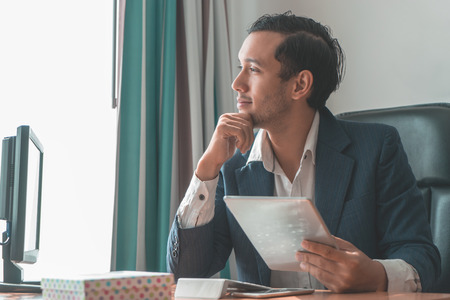 Photo pour Dreamy smiling business man happily looking out the windows - image libre de droit