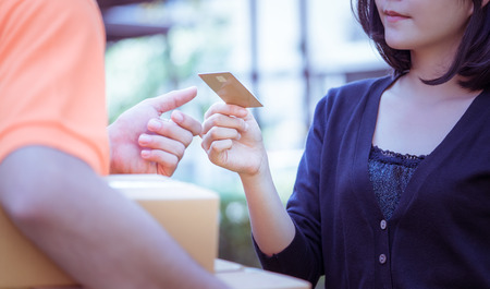 Photo pour Woman is using credit card to pay for online delivery - image libre de droit